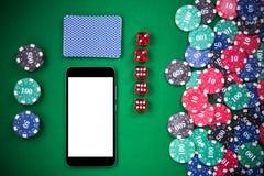 Teléfono móvil en la tabla del póker del casino, en la línea juego falso encima de plantilla fotografía de archivo