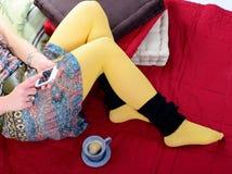 Teléfono móvil en las piernas de una mujer joven Foto de archivo libre de regalías