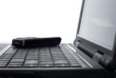 Teléfono móvil en una computadora portátil Fotografía de archivo