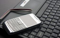 Teléfono móvil en una computadora portátil Foto de archivo libre de regalías