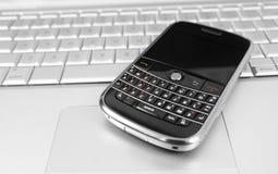 Teléfono móvil en una computadora portátil Imagen de archivo libre de regalías