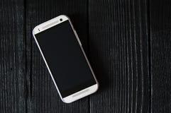 Teléfono móvil en una tabla de madera negra Imagen de archivo libre de regalías