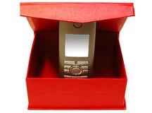 Teléfono móvil gris y caja de cartón roja. Fotos de archivo libres de regalías