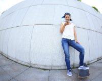 Teléfono móvil joven del uso del monopatín Imágenes de archivo libres de regalías
