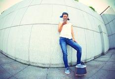 Teléfono móvil joven del uso del monopatín Fotos de archivo libres de regalías