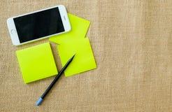 Teléfono móvil, lápiz, y libreta en fondo de la harpillera fotografía de archivo libre de regalías