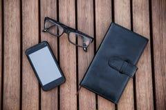 Teléfono móvil, libreta, vidrios en la tabla de madera Foto de archivo libre de regalías