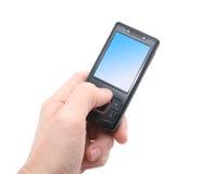 Teléfono móvil negro en mano izquierda Fotos de archivo libres de regalías
