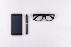 Teléfono móvil, pluma y lentes Imagen de archivo libre de regalías