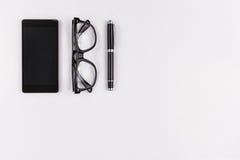 Teléfono móvil, pluma y lentes en el fondo blanco Fotografía de archivo libre de regalías