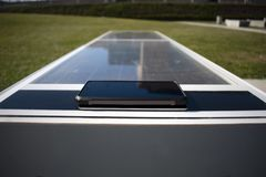 Teléfono móvil que carga remotamente en un banco solar imagenes de archivo