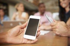 Teléfono móvil que es utilizado por el arquitecto In Meeting imágenes de archivo libres de regalías