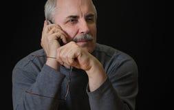 Teléfono móvil que escucha del hombre caucásico Foto de archivo libre de regalías