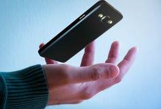 Teléfono móvil que flota sobre la mano fotos de archivo