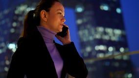 Teléfono móvil que habla de la empresaria contra rascacielos moderno almacen de metraje de vídeo