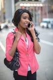 Teléfono móvil que habla de la mujer afroamericana negra en ciudad Imagen de archivo libre de regalías