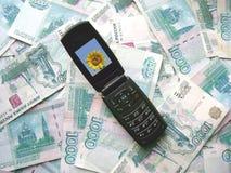 Teléfono móvil que pone en billetes de banco de Rusia Fotos de archivo