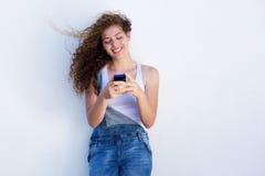 Teléfono móvil que se sostiene adolescente feliz y sonrisa con soplar del pelo Fotos de archivo libres de regalías