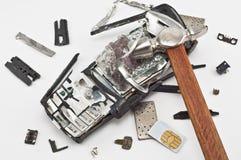 Teléfono móvil roto con un martillo fotografía de archivo
