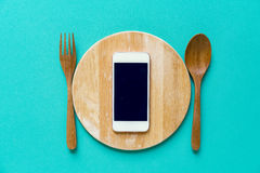 Teléfono móvil servido en la placa de madera Imagen de archivo