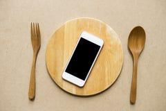 Teléfono móvil servido en la placa de madera Fotografía de archivo