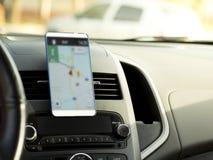 Teléfono móvil situado en el centro de la consola del vehículo Teléfono de pantalla en blanco en el coche fotografía de archivo