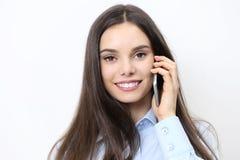 Teléfono móvil sonriente feliz de la mujer que habla en blanco Foto de archivo libre de regalías