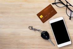 Teléfono móvil, tarjeta de crédito y llave en el fondo de madera de la textura Imagen de archivo libre de regalías