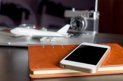 Teléfono móvil vacío en blanco con los objetos del viaje Foto de archivo
