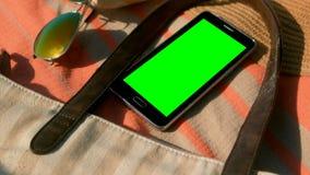 Teléfono móvil y accesorios en la manta de la comida campestre en la playa en un día soleado