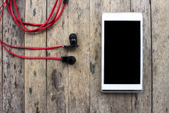 Teléfono móvil y auricular en fondo de madera Fotos de archivo