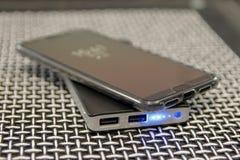 Teléfono móvil y banco inalámbrico del poder de Qi foto de archivo