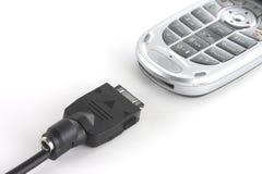Teléfono móvil y cable de la sinc. Foto de archivo