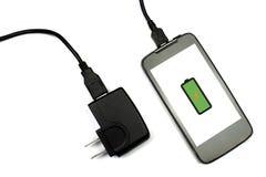 Teléfono móvil y cargador en el fondo blanco, aislado Fotografía de archivo libre de regalías