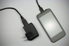 Teléfono móvil y cargador en fondo gris Foto de archivo
