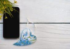 Teléfono móvil y corazón de madera hechos a mano Visión superior Concepto: Amo la comunicación/las conversaciones/vida/música/ imagen de archivo libre de regalías