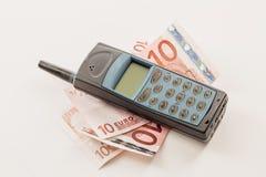 Teléfono móvil y dinero en el fondo blanco Fotos de archivo libres de regalías