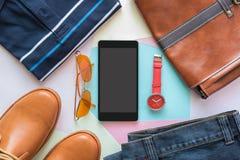 Teléfono móvil y endecha plana de la moda casual del ` s de los hombres en el woode blanco Imagen de archivo