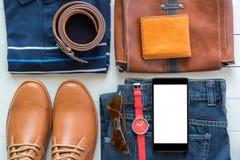 Teléfono móvil y endecha plana de la moda casual del ` s de los hombres en el woode blanco Foto de archivo