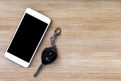 Teléfono móvil y llave en el fondo de madera de la textura Fotos de archivo libres de regalías