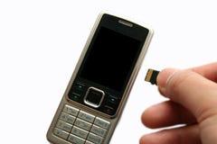 Teléfono móvil y mano con la tarjeta de memoria Fotografía de archivo libre de regalías