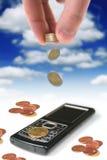 Teléfono móvil y monedas Imagenes de archivo