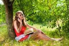 Teléfono móvil y mujer sonriente feliz hermosa Foto de archivo libre de regalías