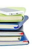 Teléfono móvil y pila de libros Foto de archivo libre de regalías