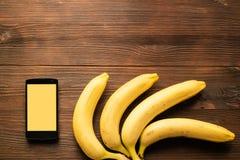 Teléfono móvil y plátanos en una tabla de madera, visión superior fotografía de archivo