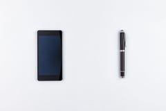 Teléfono móvil y pluma en el fondo blanco Imagen de archivo