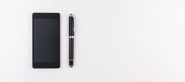 Teléfono móvil y pluma en el fondo blanco Foto de archivo libre de regalías