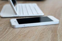 Teléfono móvil y tableta blancos con el teclado en la tabla Imagen de archivo