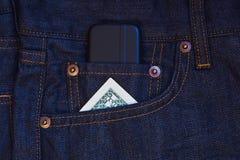 Teléfono móvil y un billete de banco del dólar Fotos de archivo