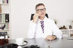 Teléfono masculino de Calling Client Through del médico foto de archivo libre de regalías